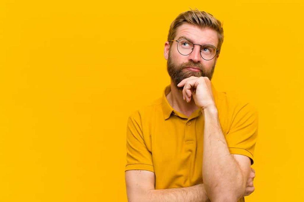 גבר עם זקן ומשקפיים על רקע צהוב חושב על שאלה