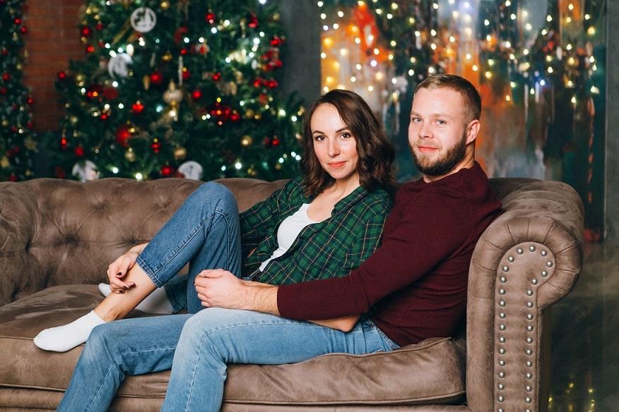 זוג יושב על הספה בסלון ומסתכל למצלמה בחורף