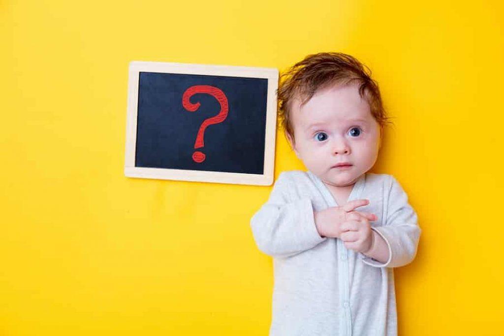תינוקת קטנה עם סימן שאלה ליד הראש על רקע צהוב