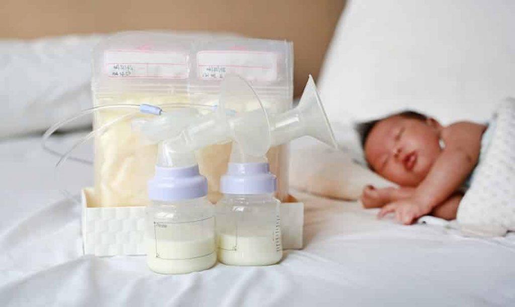 תינוק אסייתי שוכב ליד משאבות חלב אם