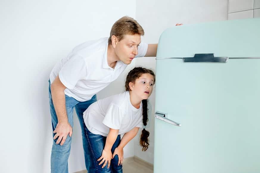 אבא ובת מסתכלים לתוך המקרר עם מבט מלא בסקרנות