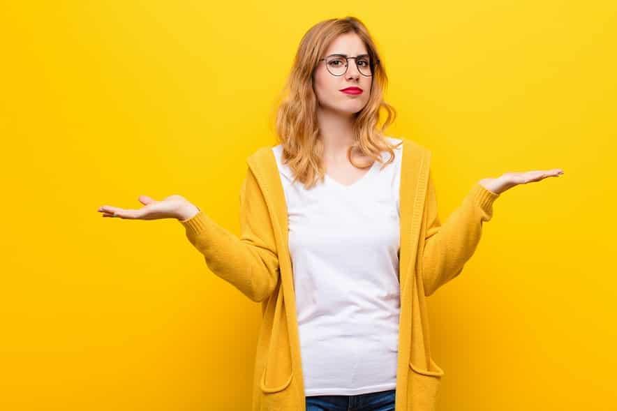 אישה מבולבלת עם שאלות על רקע צהוב