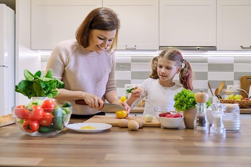 אמא מלמדת את הבת שלה דברים שונים במטבח עם ירקות