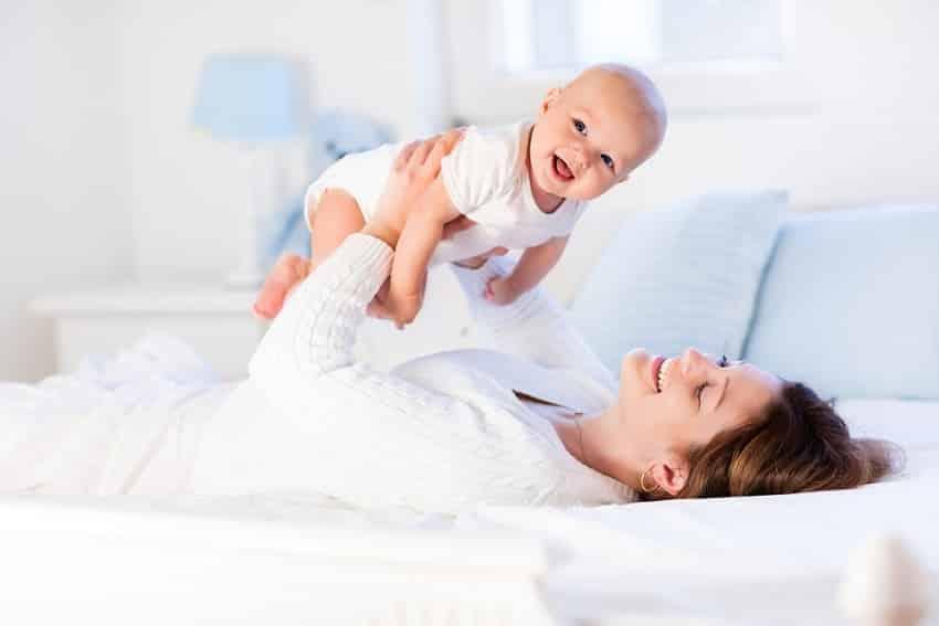 אמא משחקת עם התינוק שלה במיטה על רקע לבן בהיר