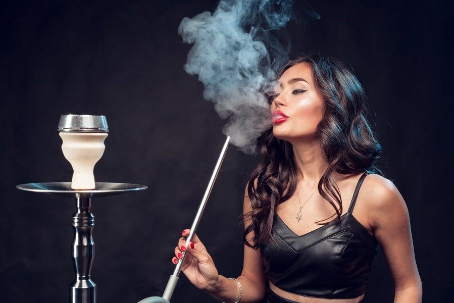 בחורה אסייתית עם עליונית שחורה מעור מעשנת מצינור