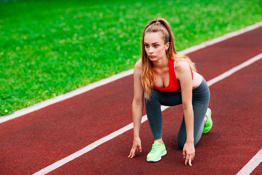 בחורה בלונדינית צעירה יושבת על מסלול ריצה בהיכון