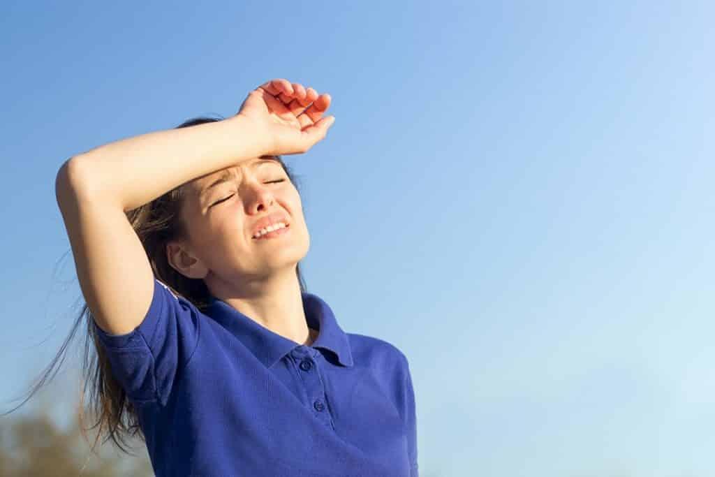 בחורה עומדת בחוץ ושמה את היד על הראש בגלל החום