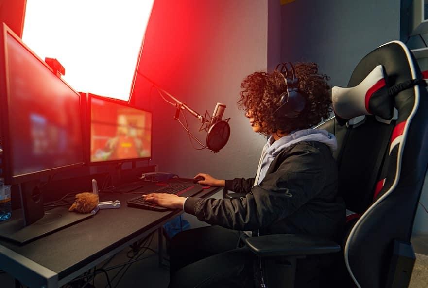 בחורה עם תלתלים משחקת במחשב על כמה מסכים במקביל