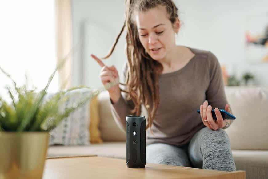 בחורה צעירה עם ראסטות מדברת עם מכשיר חשמלי