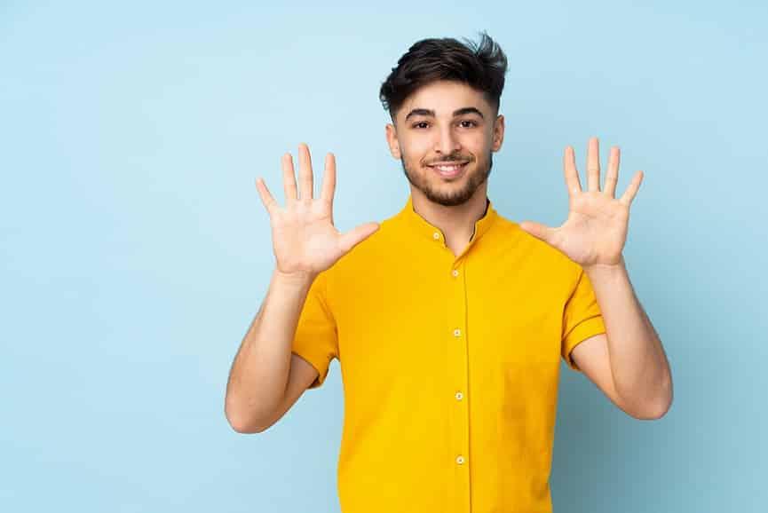 בחור ממוצא מזרחי עם חולצה צהובה מראה את המספר 10 בידיים