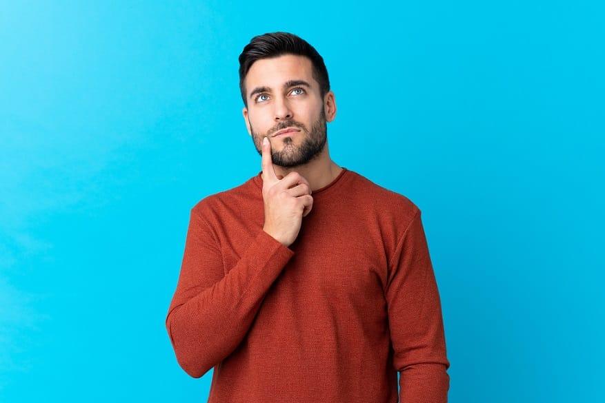 בחור עם סוודר בורדו חושב על שאלה על רקע כחול בהיר