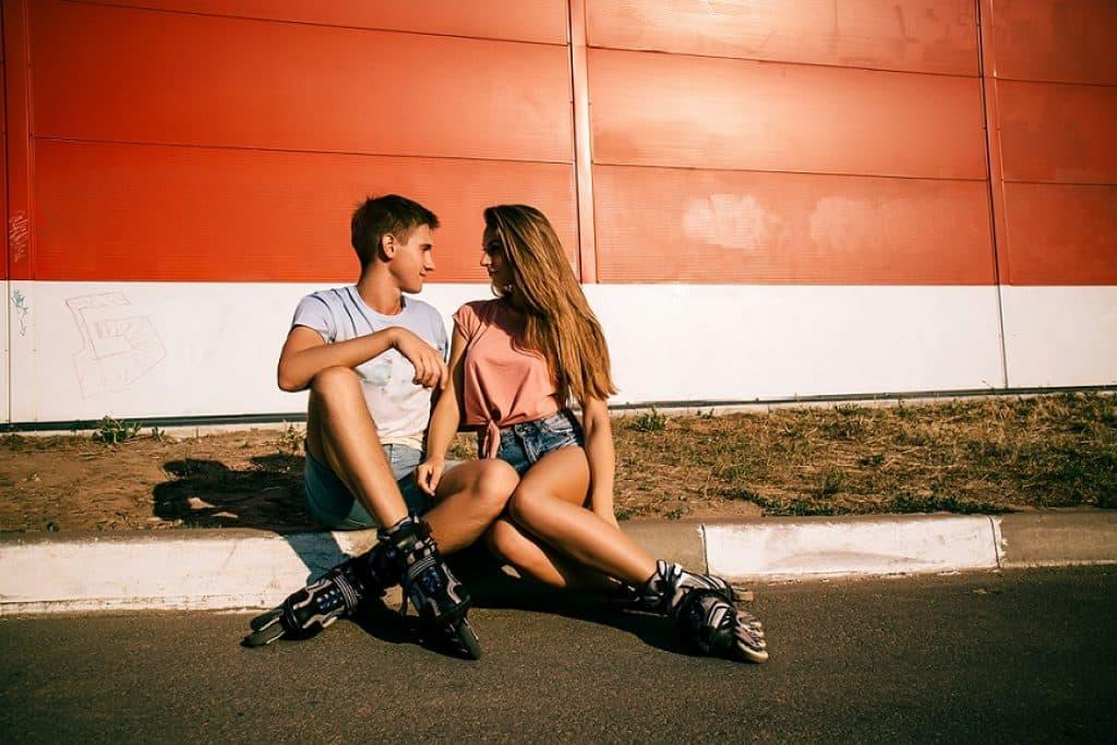 זוג צעיר יושב על המדרכה עם מבט מאוהב