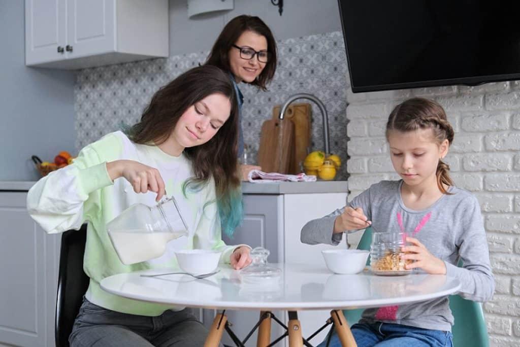 ילדות נהנות ואוכלות במטבח בזמן שאמא מנקה