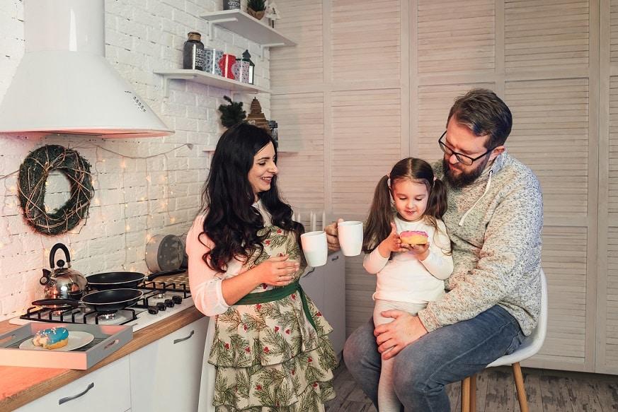 משפחה של אמא אבא וילדה יושבים במטבח ושותים תה חם