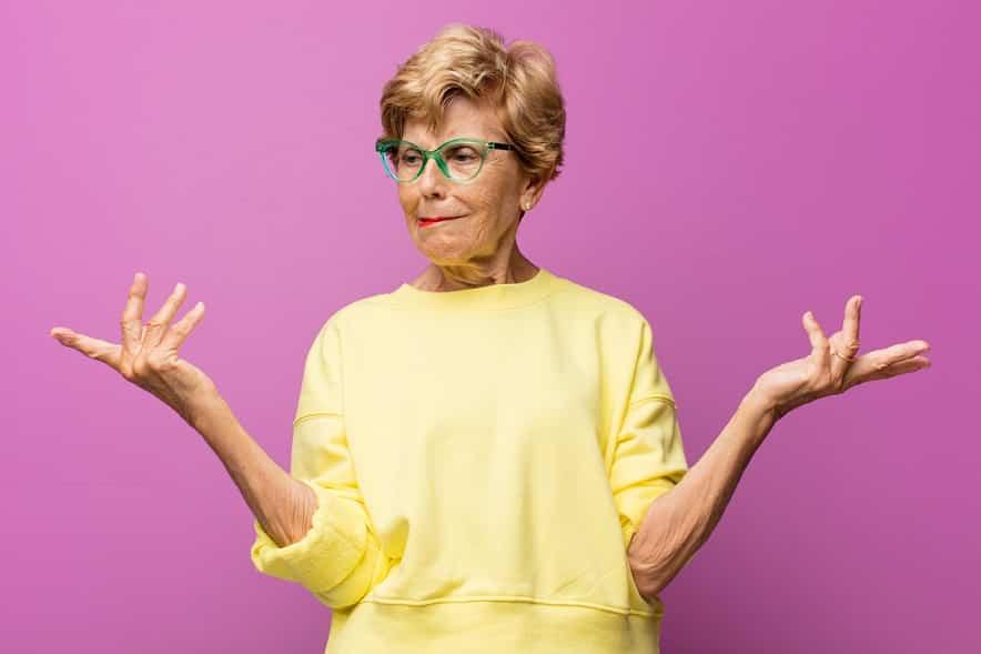 סבתא עם חולצה צהובה עושה תנועה של שאלה על רקע ורוד