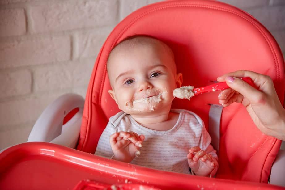 תינוק שבע מחייך עם הרבה אוכל על הפנים