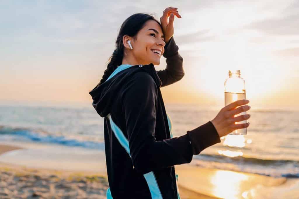בחורה נוגעת במצח ושותה מים בזמן אימון בחוף הים