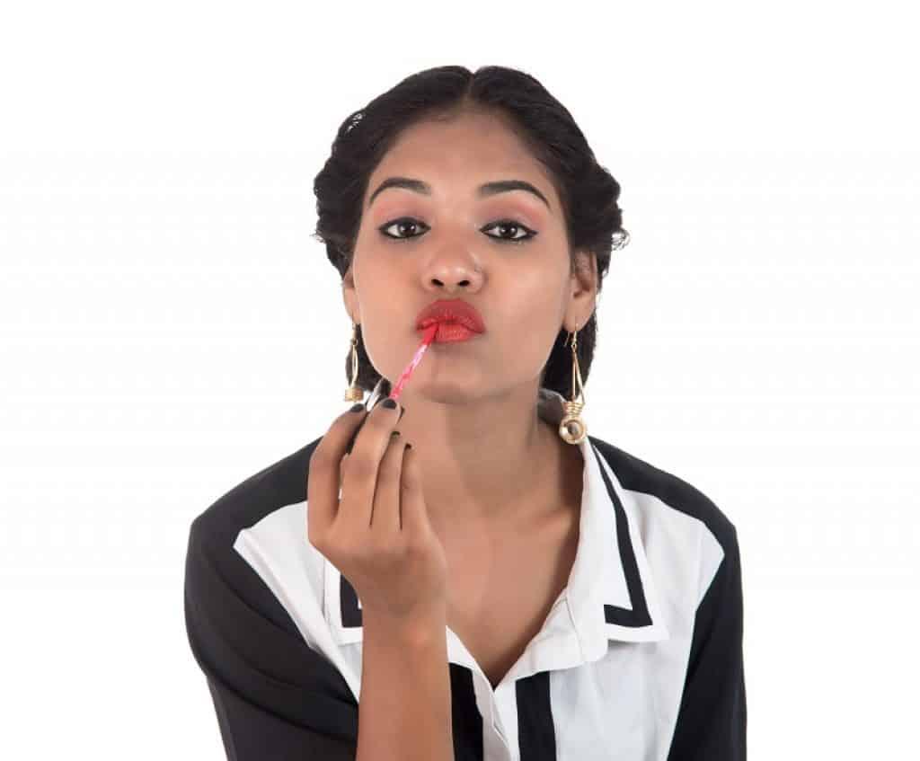 בחורה עם חולצה מכופתרת מורחת צבע על השפתיים