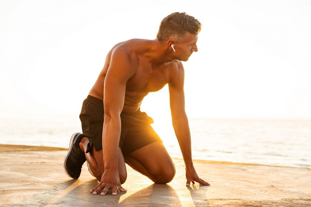 בחור עם אוזניות ספורט יושב על הברכיים לקראת ריצה אינטנסיבית בחוף הים