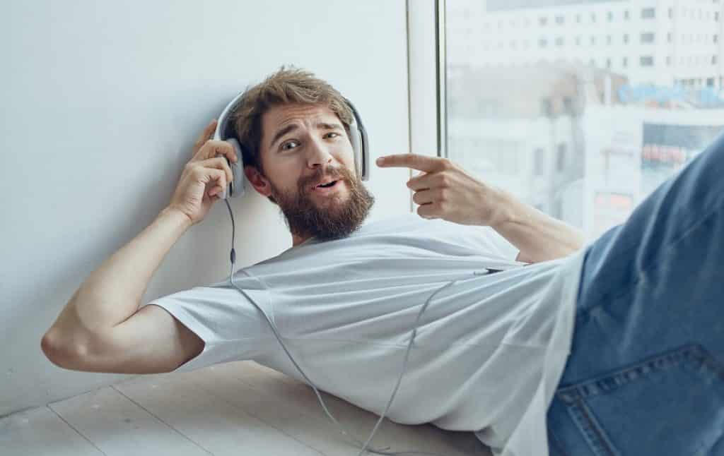 בחור עם ג'ינס שוכב מצביע על האוזן