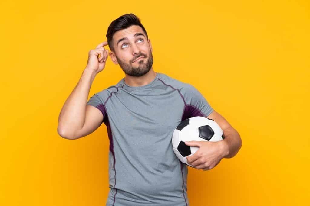 בחור עם זקן מחזיק כדור ביד במבט של שאלה