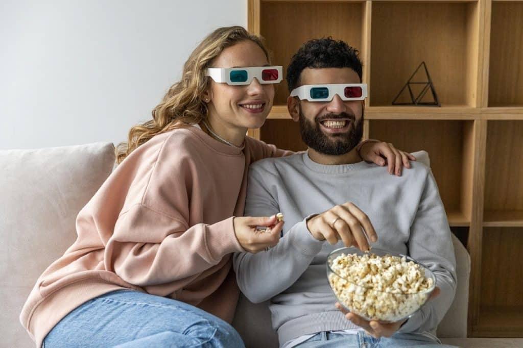 גבר ואישה יושבים בסלון עם משקפי תלת מימד
