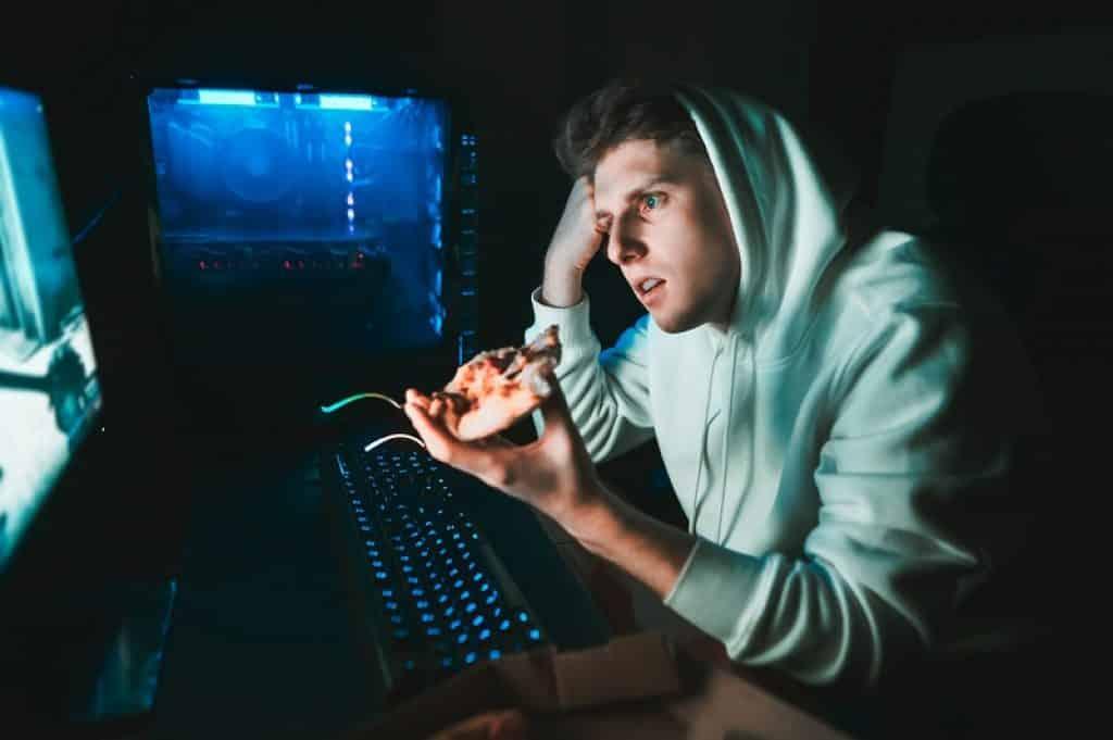 גיימר עם כובע על הראש אוכל פיצה מול המחשב