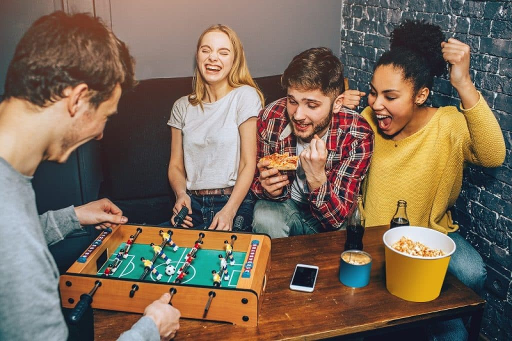 חבורה של ארבעה צעירים משחקים אוכלים פיצה ונהנים