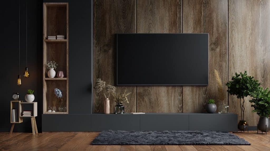 חדר בעיצוב עץ עם שטיח אפור וכוורת מלבנית שמתאימה לטלוויזיות 55 אינץ'