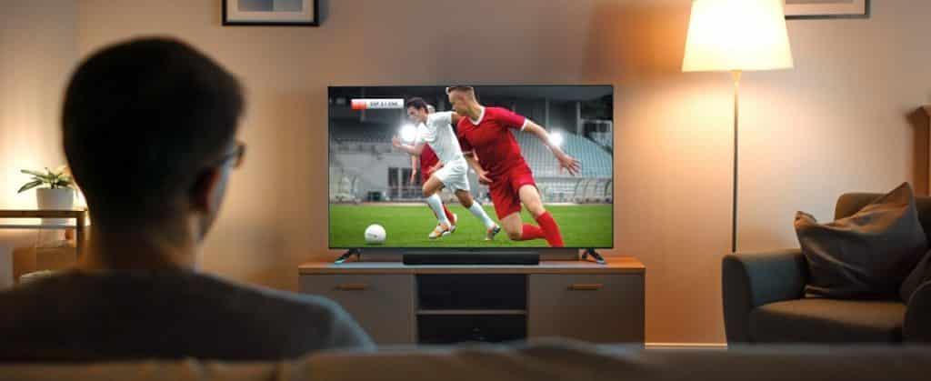 צופה במשחק כדורגל בסלון מול הטלוויזיה