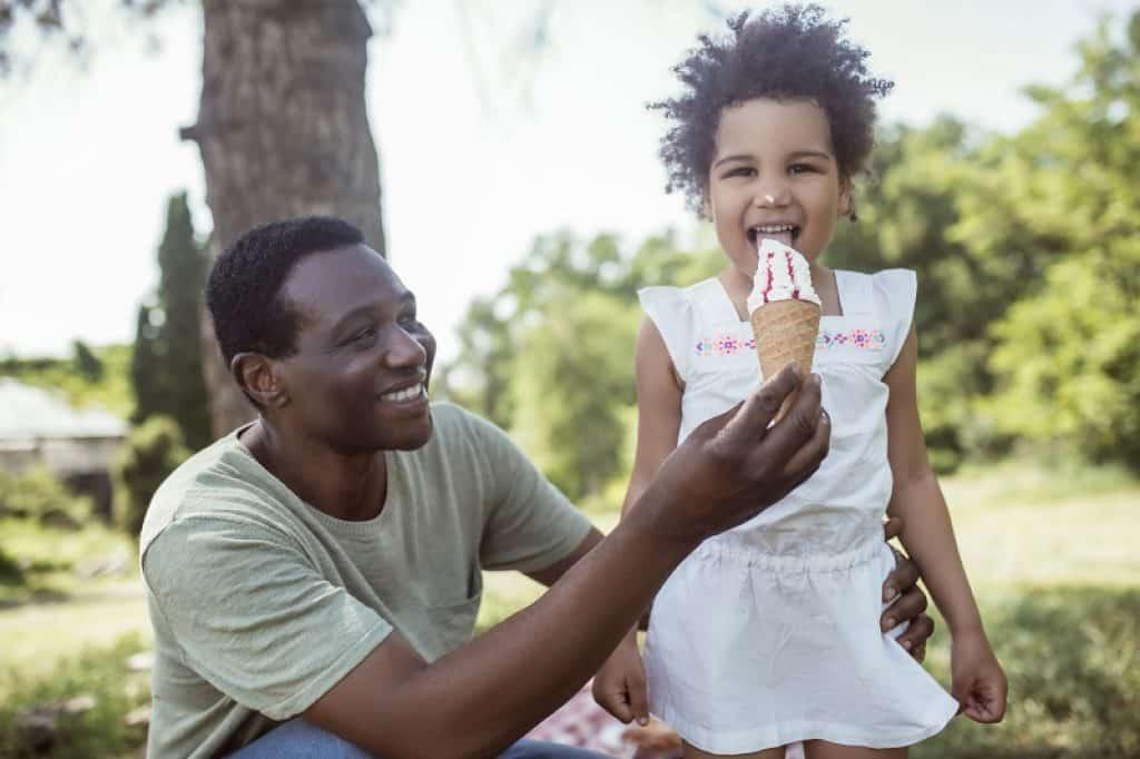 אבא מאכיל את הילדה בחיק הטבע ושניהם נראים שמחים