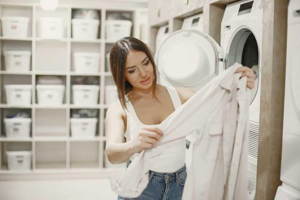 אישה מוציאה בגדים נקיים מהמייבש