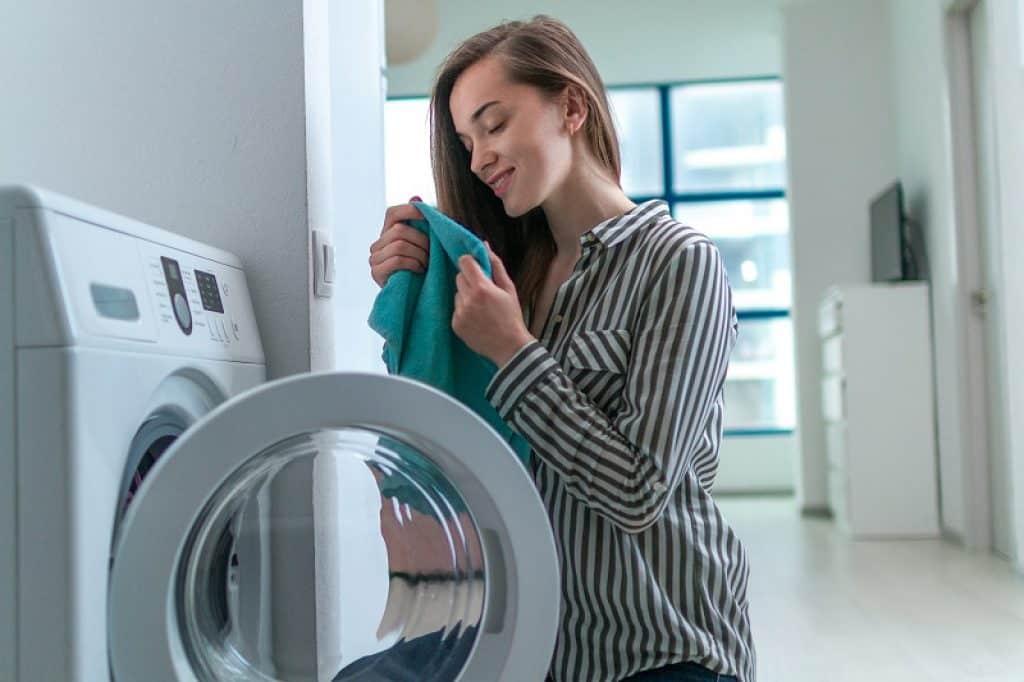 אישה מריחה בגדים ריחניים שיצאו מהכביסה