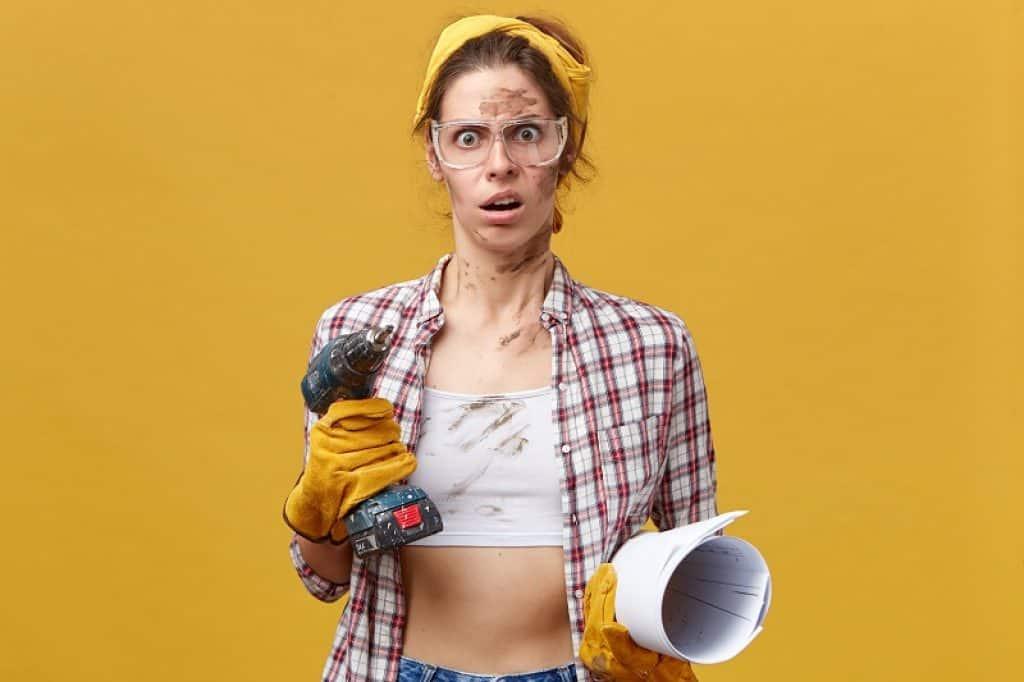 אישה עם בגדי עבודה על רקע צהוב ומבט של שאלה