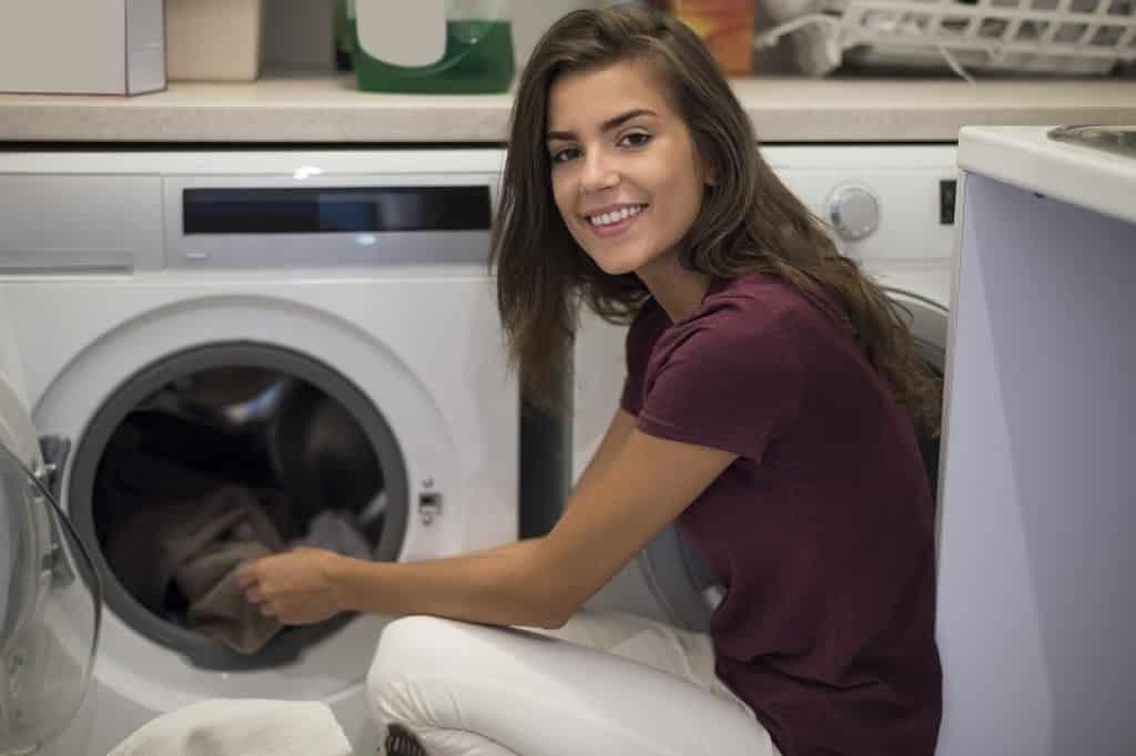 אישה עם חולצה בורדו ממלאה מכונה עם פתח חזית