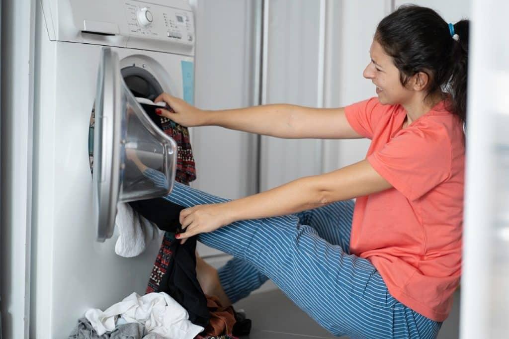 אישה עם חולצה ורודה דוחפת בגדים עם הרגל