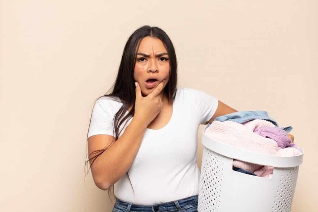 אישה עם חולצה לבנה וסל כביסה ביד במבט שאלה