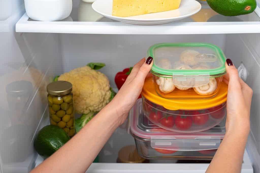 אישה עם לק שחור באצבעות מסדרת קופסאות אוכל