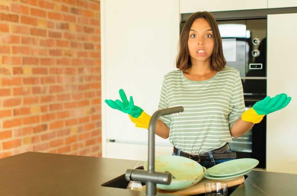 אישה עם ערימת כלים מלוכלכים בכיור שואלת שאלה