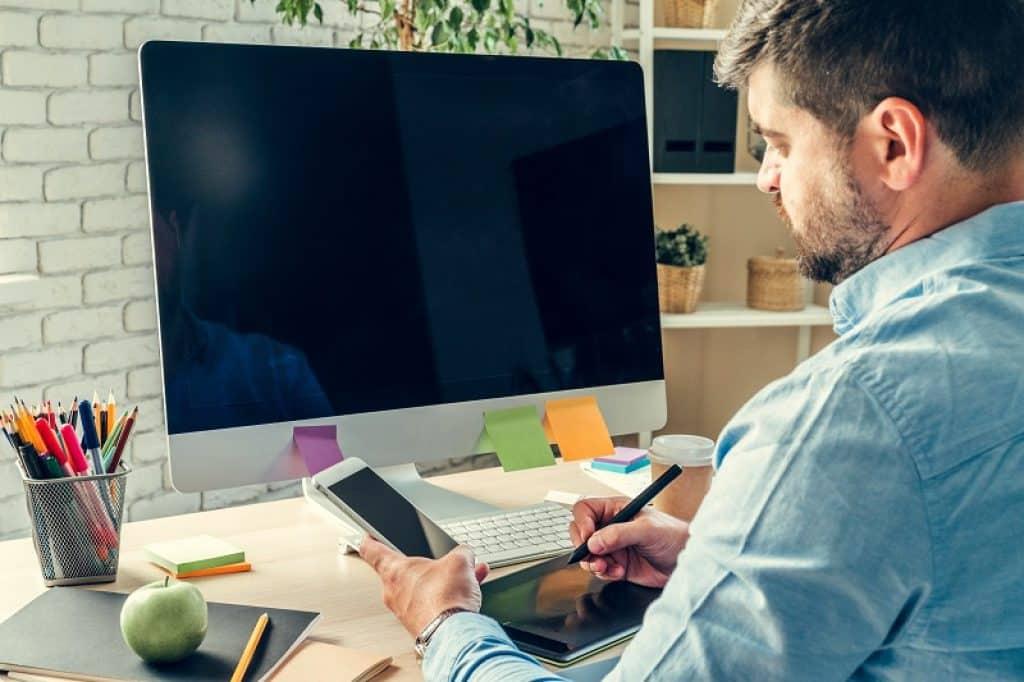 איש יושב במשרד מול מסך מחשב עם טלפון ביד