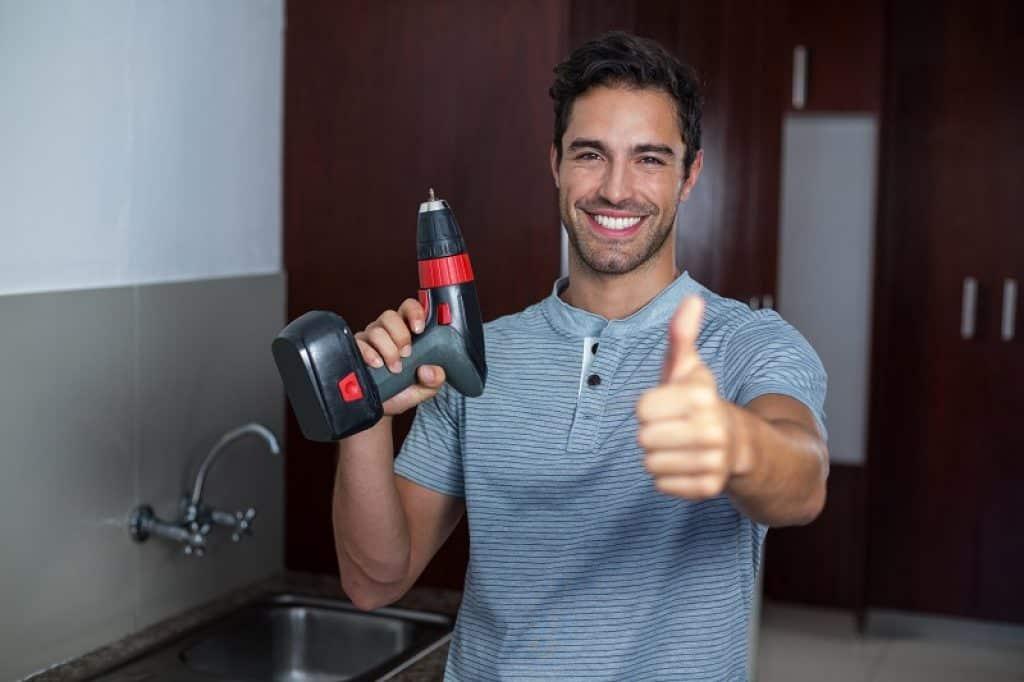 איש שמח עם אגודל למעלה אחרי שביצע עבודות שיפוץ מוצלחות בבית