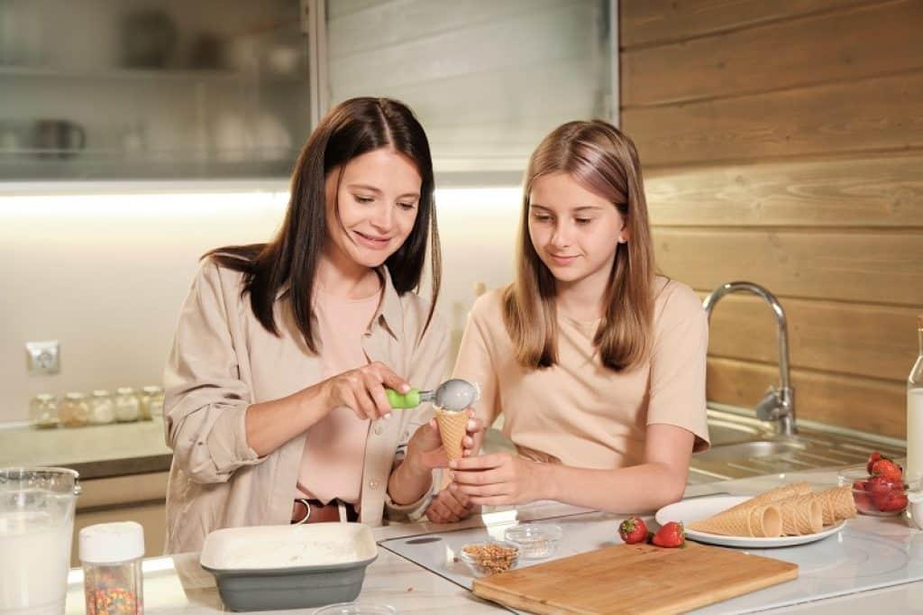 אמא ובת מכינות גביעים עם ג'לאטו שהכינו במכונת גלידה
