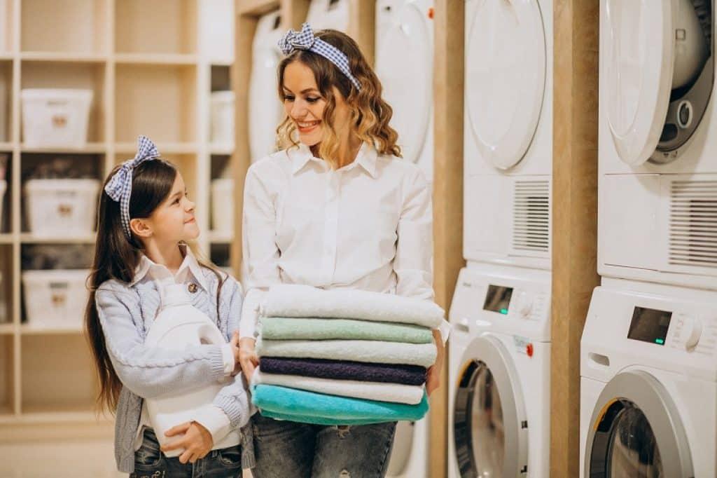 אמא וילדה עם כביסה מקופלת במכבסה