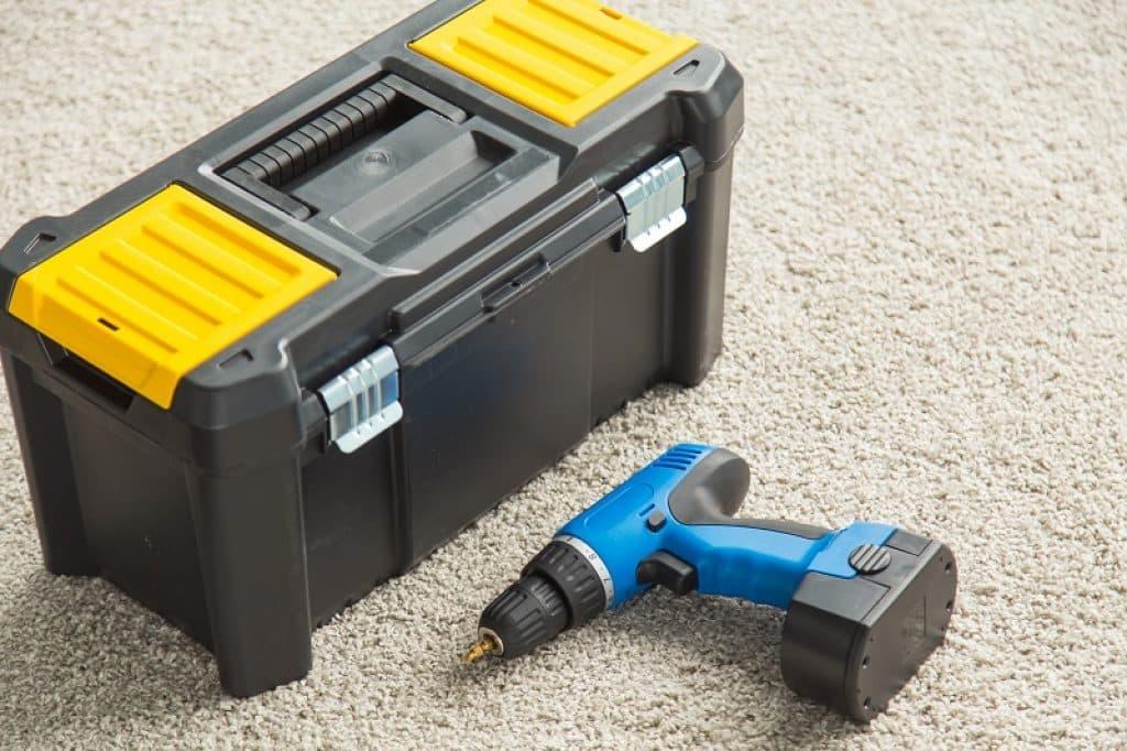 ארגז כלי עבודה שחור צהוב על הרצפה כולל מברגה כחלחלה