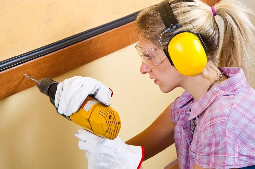 בחורה בלונדינית עם אוזניות חוסמות רעש צהובות מתקנת קיר