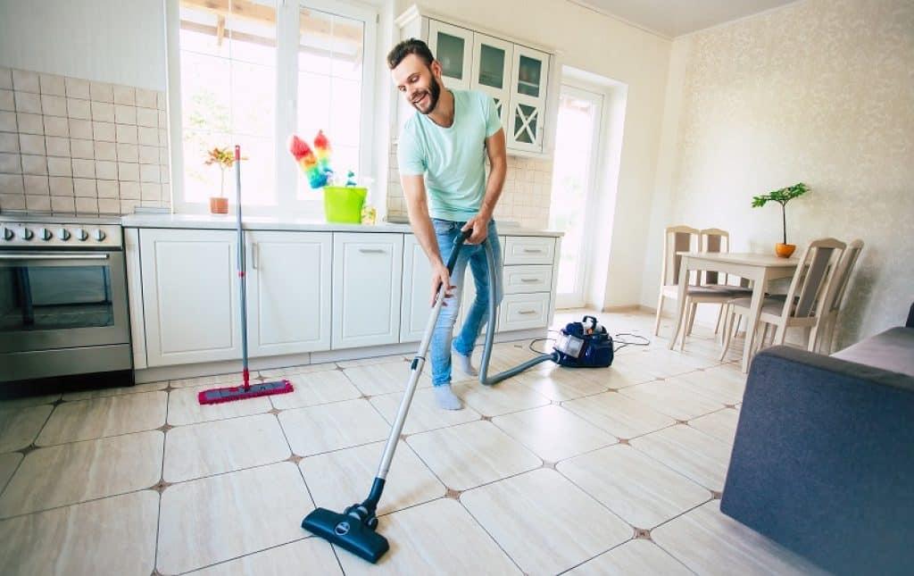 בחור במצב רוח שמח מנקה את הרצפה של המטבח
