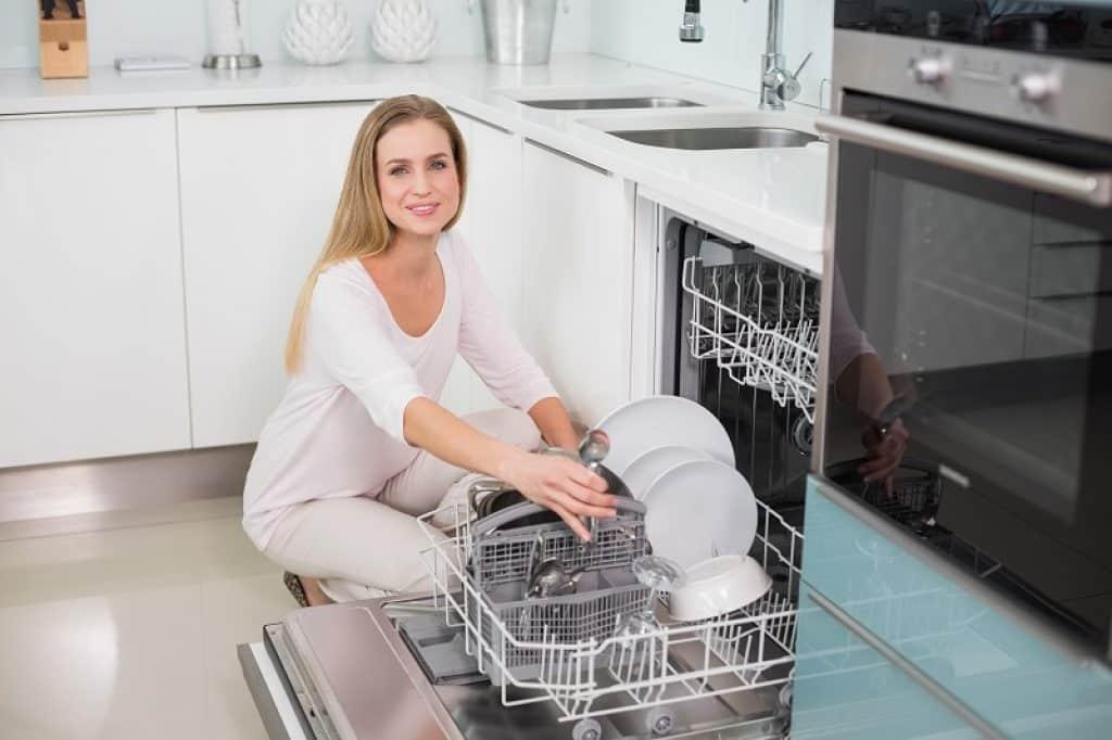 אישה יושבת על הרצפה במטבח עם חיוך שהכלים נקיים