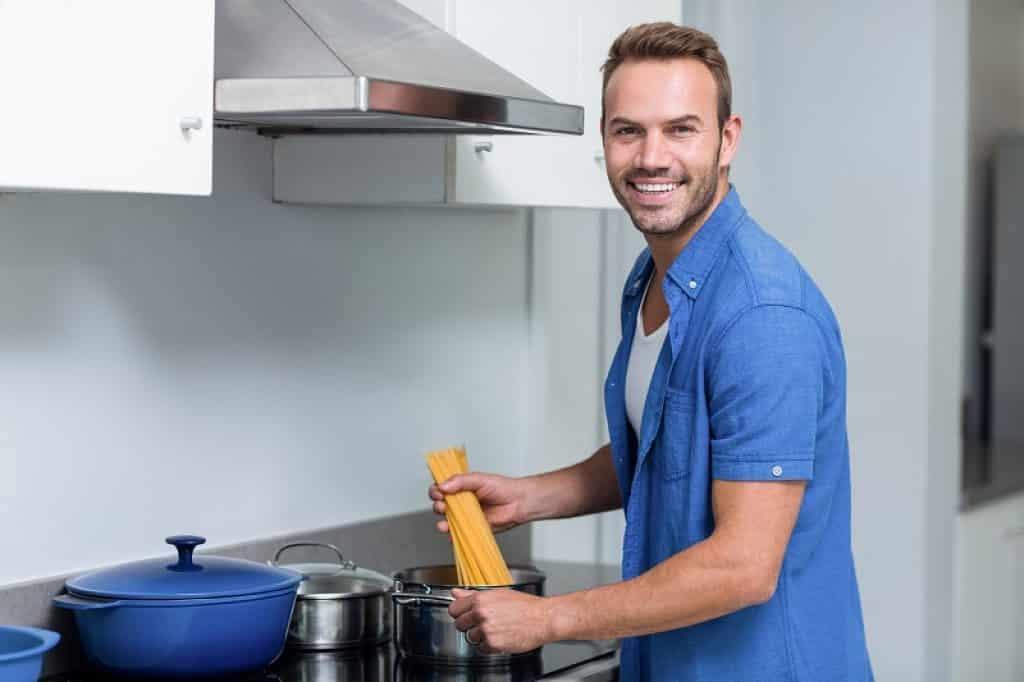 בחור עם חולצה כחולה מכין ספגטי ומחייך