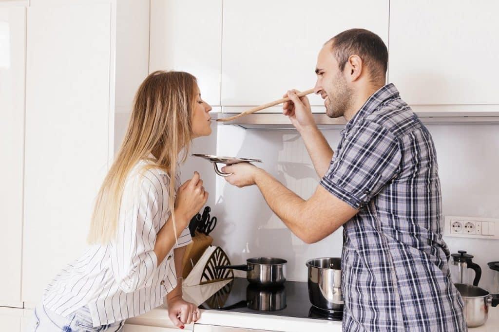 בחור עם חולצה משובצת מאכיל בחורה תוך כדי בישולים