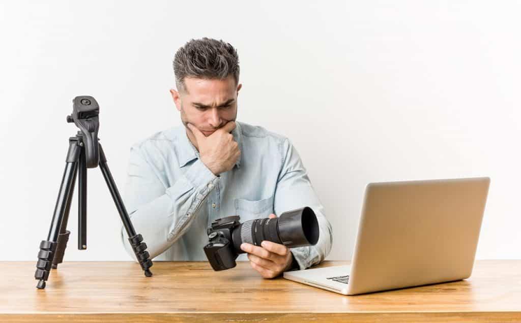 גבר במבט של שאלה יושב ומחזיק מצלמה מול מחשב נייד